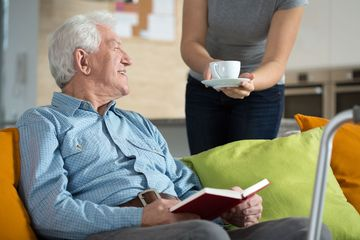 An elderly man reading an book while carer brings a cup of tea